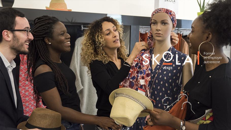 5 vendeurs dans un magasin de vêtement qui assiste à une démonstration de nouage de foulard sur un manequin